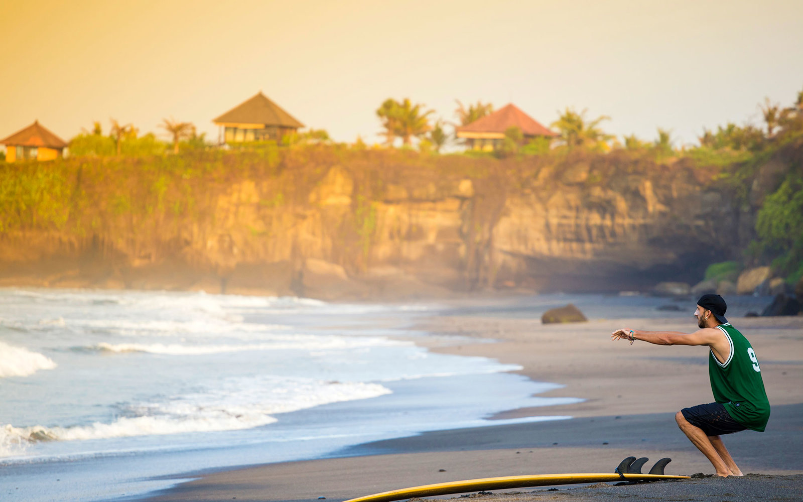 Indonesia, Bali, surfer on the beach doing a knee bend
