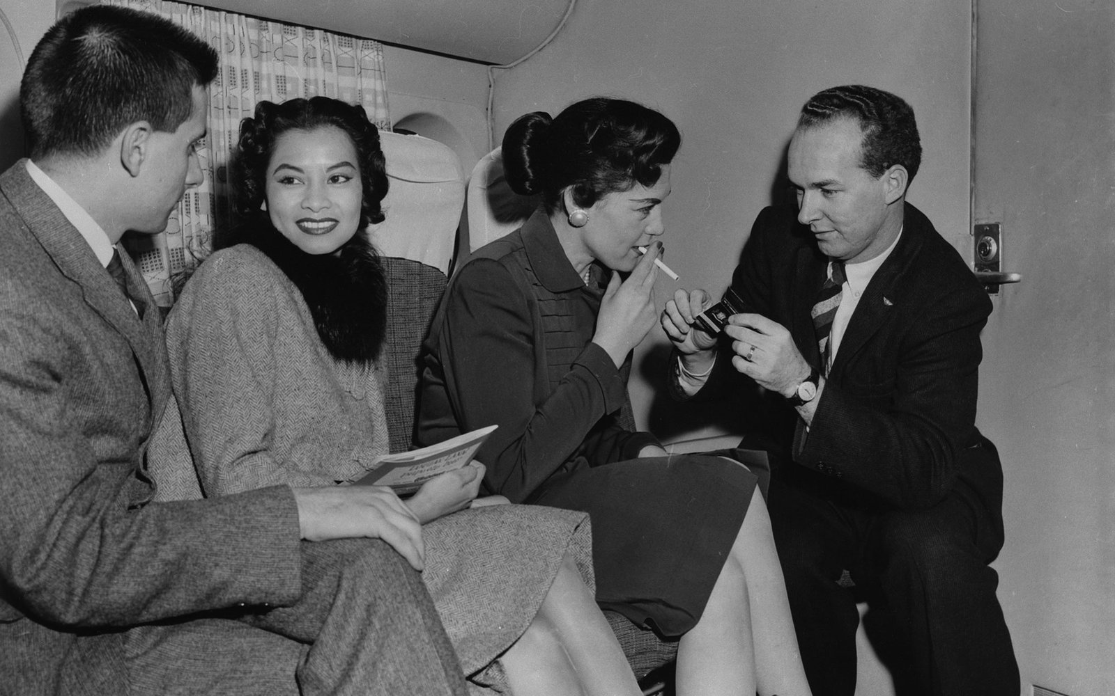 NEW YORK - MID 1950's:  Passengers enjoy a relaxing smoke on a Transocean Air lines Boeing 377 Stratocruiser in the mid 1950's. Transocean Air lines flew between 1946 and 1962 and was a pioneer discount airline. (Photo by Michael Ochs Archive/Getty Images