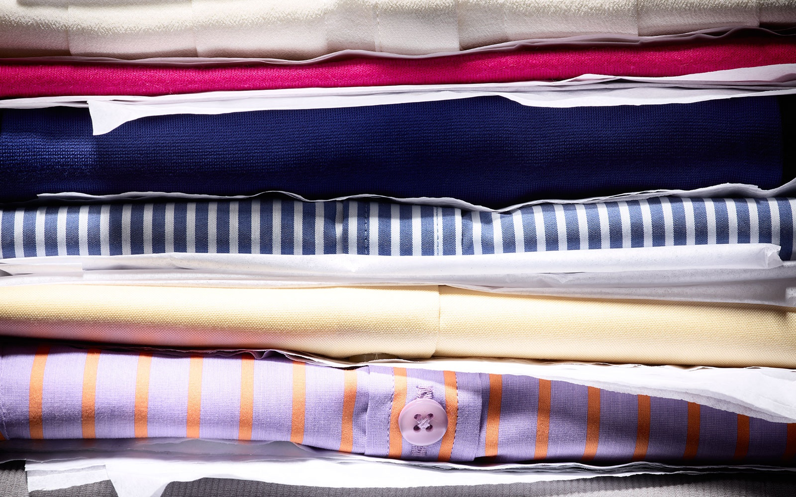 folded shirts stacked for packing suitcase