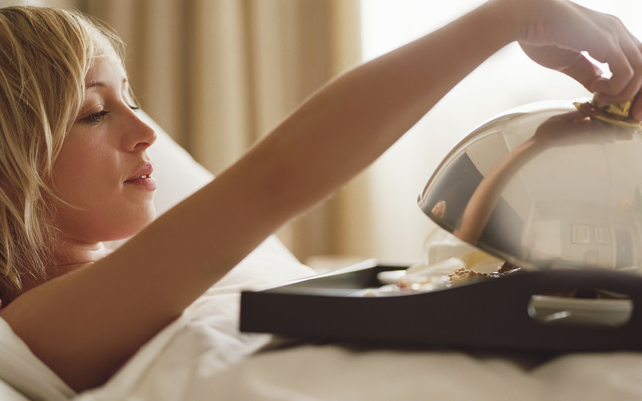 Woman lying in bed lifting dome on breakfast tray