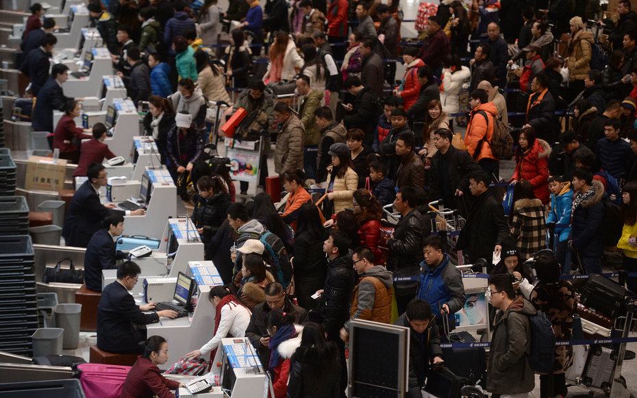 This picture taken on February 4, 2015 shows passengers checking in at the service counters in Beijing Capital International Airport on the first day of China's spring festival travel rush in Beijing. The travel period known as 'chunyun' is the world's la