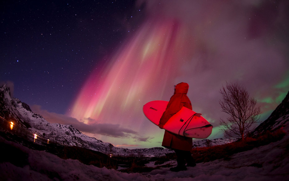 A surfer looks at the Northern lights ( aurora borealis ) illuminating the sky over the snow covered beach of Unstad, on Lofoten Islands, Arctic Circle, on March 14, 2016.  Surfers from all over the world come to Lofoten island to surf in extrem conditio