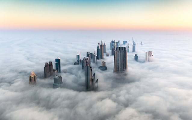 Aerial view over Dubai with Index Tower, Emirates Towes and the Sheikh Zayed Road skyline sitting in a thick fog blanket in front of a red sunrise and blue sky. Dubai, United Arab Emirates