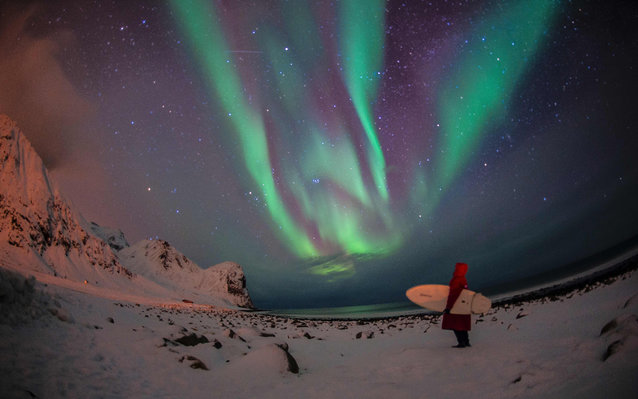A surfer looks at northern lights ( aurora borealis ) at the snow covered beach of Unstad, on Lofoten Island, Arctic Circle, on March 9, 2016.  Surfers from all over the world comes to Lofoten island to surf in extrem conditions. Ocean temperature is 5-6
