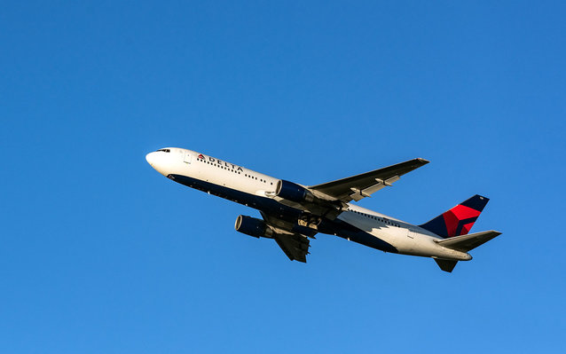 A Delta airplane against a blue sky.