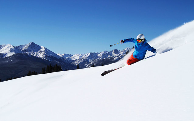 A skier comes down a mountainside.