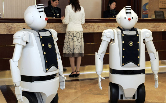 "URAYASU, JAPAN:  Hitachi's humanoid robots ""EMIEW"" greet guests at the front desk of the Sheraton Grande Tokyo Bay hotel in Urayasu, suburban Tokyo, 06 March 2006. The Sheratan and Hitachi have collaborated for a week-long promotion for their guests at th"