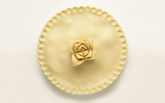 Pie with scalloped edge and decorated with pastry rose