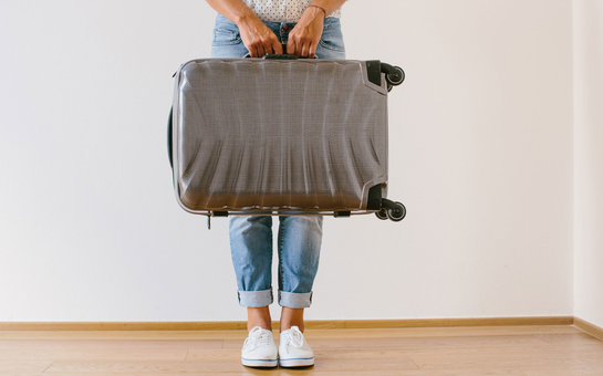 Woman assessing luggage weight
