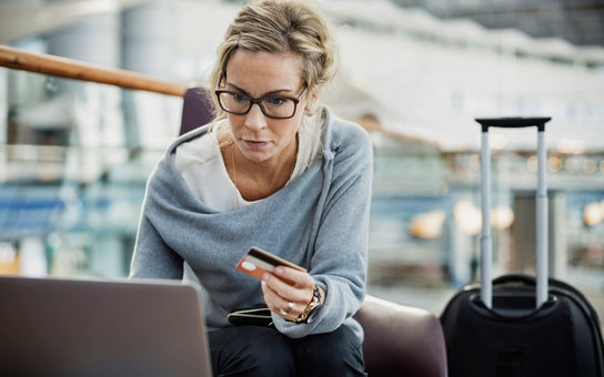 Businesswoman using credit card and laptop in airport lobby