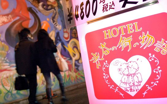 JAPAN - MARCH 01:  A couple walk past a love hotel in Tokyo's Shibuya district Monday, February 28, 2005.  (Photo by Andy Rain/Bloomberg via Getty Images)