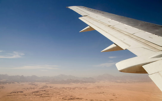 Airplane flying over a desert