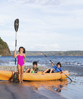 kids in a kayak on the water in Costa Rica